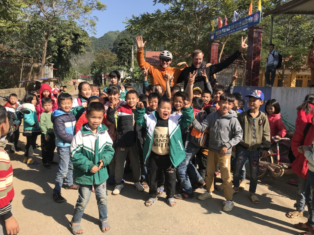 Trango athlete Skiy DeTray and a friend smiling with a large group of local children in Huu Long, Vietnam.