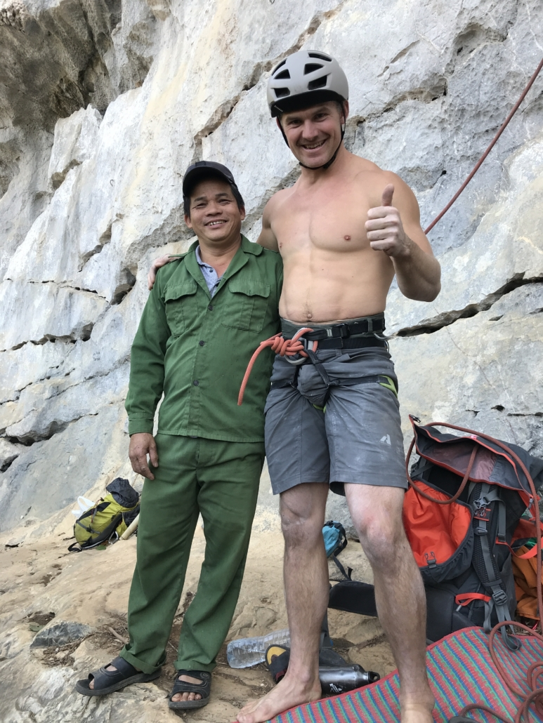 A climbing smiling with a local man at a crag in Huu Long, Vietnam.