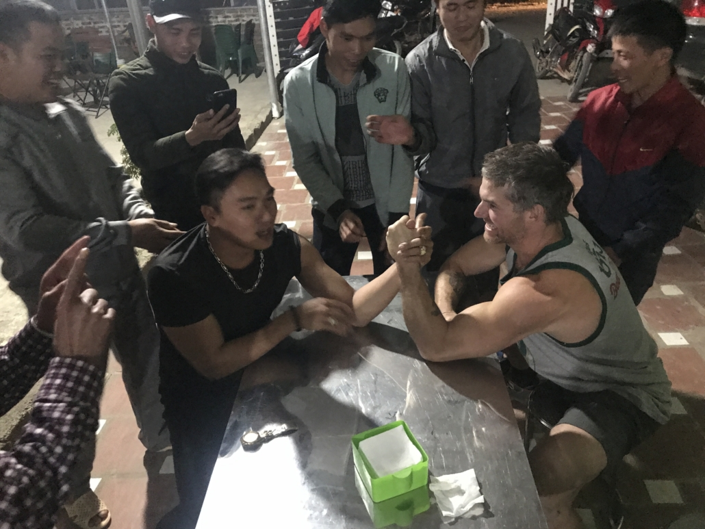 Ian arm wrestling with a group of locals on a climbing trip in Huu Long, Vietnam.
