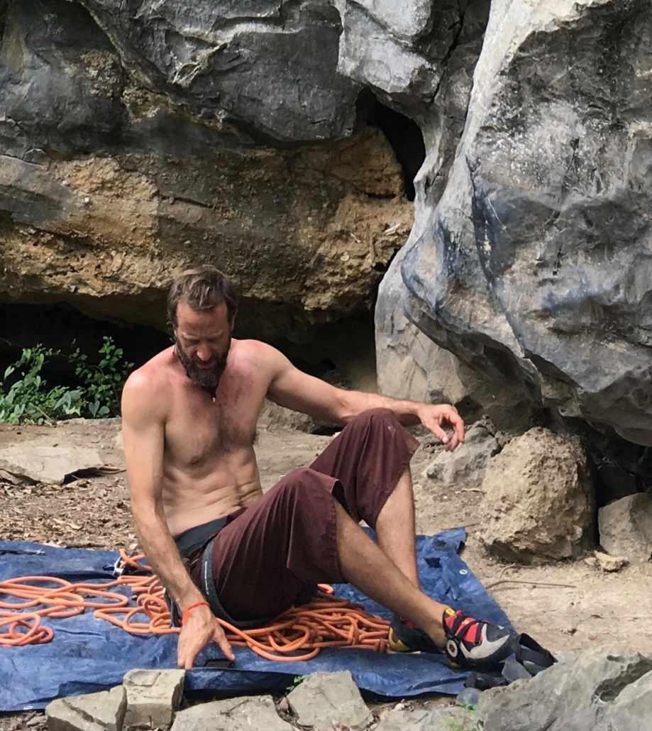 Trango athlete Skiy DeTray sitting on a tarp with a climbing rope at a crag in Huu Lung, Vietnam.