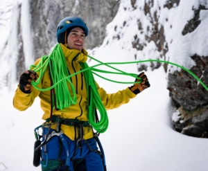 Nate Kenney flaking a green Trango Agility 9.5 with Red Flag rope while ice climbing.