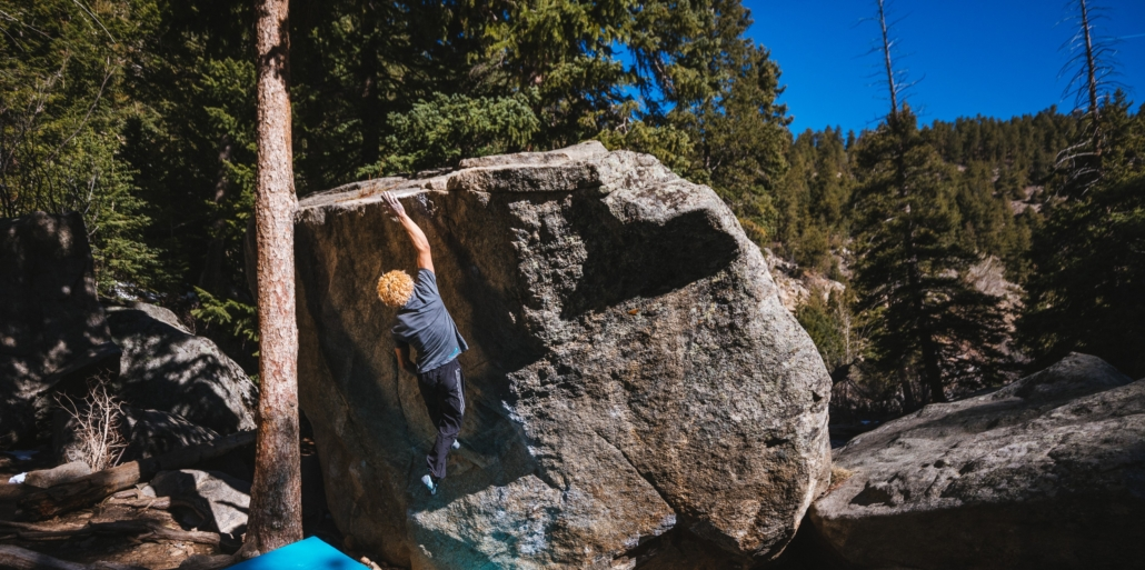 Bobby Taft-Pittman reaching for the top hold of a boulder problem in Boulder Canyon, CO. Photo by Alton Richardson.