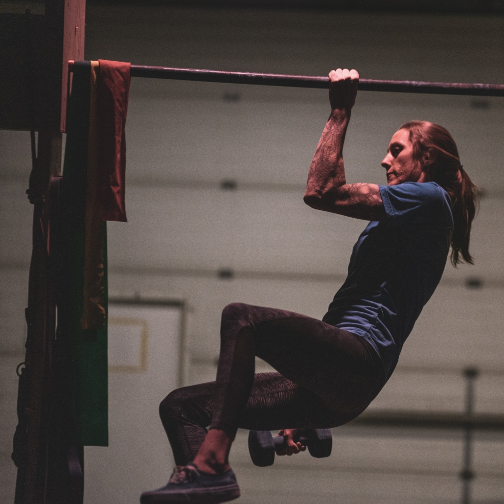 Alex Johnson hanging from a pull-up bar by one arm bent at 90 degrees while holding a small dumbbell in her other hand.